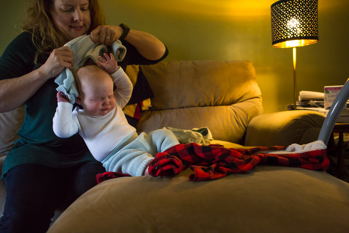 Baby scrunches his face up when mom pulls shirt over his head.