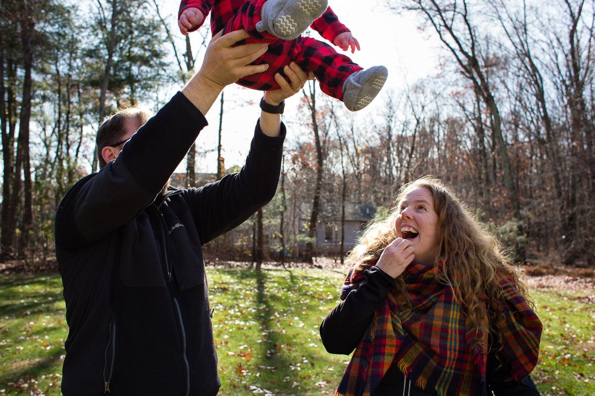 Dad lifts baby boy up to the sky while mom looks on slightly concerned.