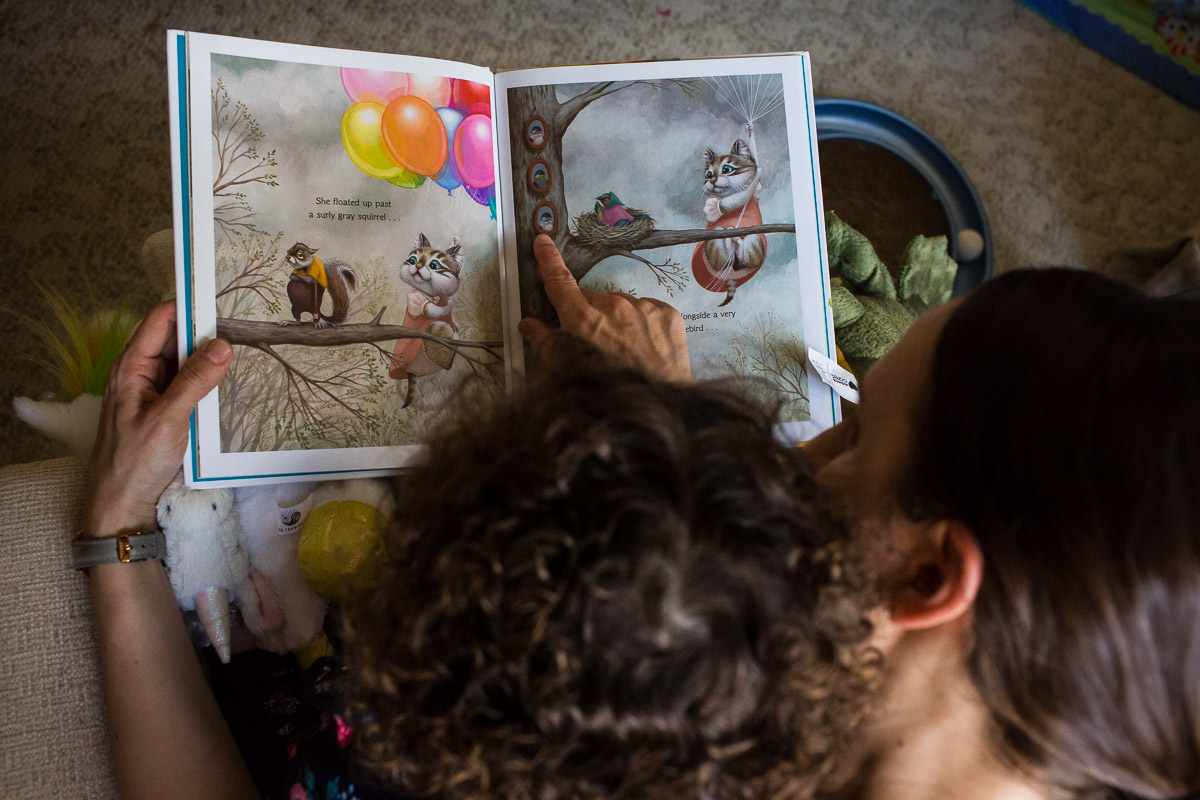 Mom reads one of daughter's favorite books, while daughter listens with her stuffed animals close by.