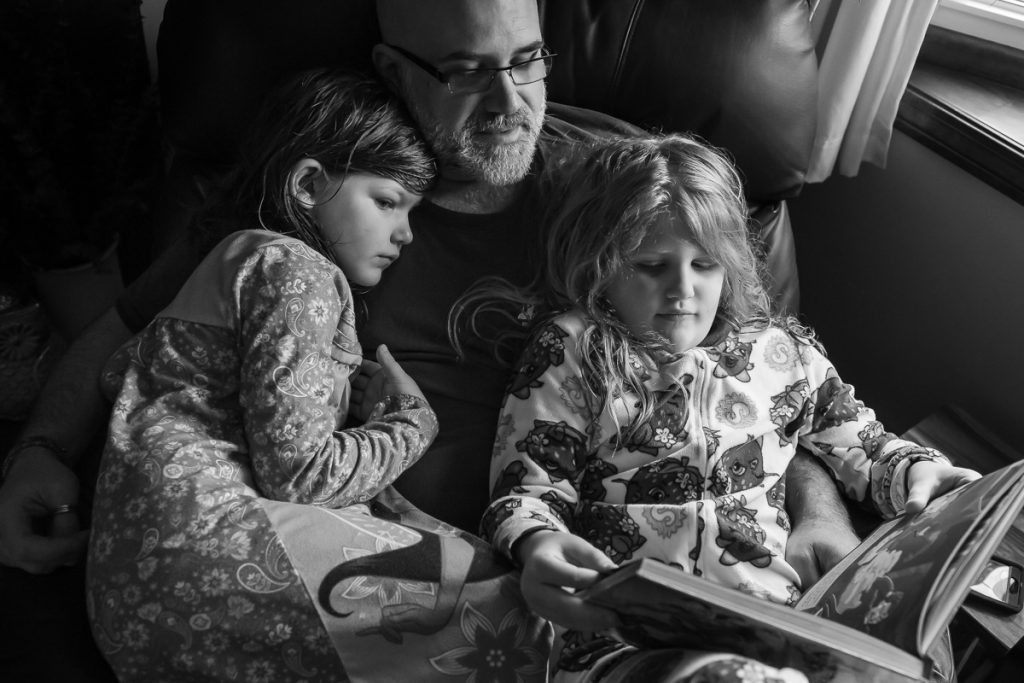 Father and daughters snuggling and reading in chair together